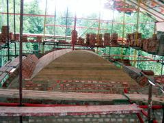 После устройства арок и выравнивания стен конструкторами было предписано выполнить замкнутый железобетонный пояс, распределяющий нагрузку равномерно по стенам, на который уже и должен был опираться свод. Завершив пояс и смонтировав опалубку свода по выданным чертежам, приступили к его кладке. Он представляет собой сомкнутый свод, толщиной 25 см, усиленный гуртами толщиной 38 см. Для большей надежности кладку армировали кладочной сеткой через каждые четыре ряда. Снаружи по периметру свод стянут мощным бандажем из сваренной вдвое арматуры  диаметром 38 мм и прутом прямоугольного сечения 60х30(мм).